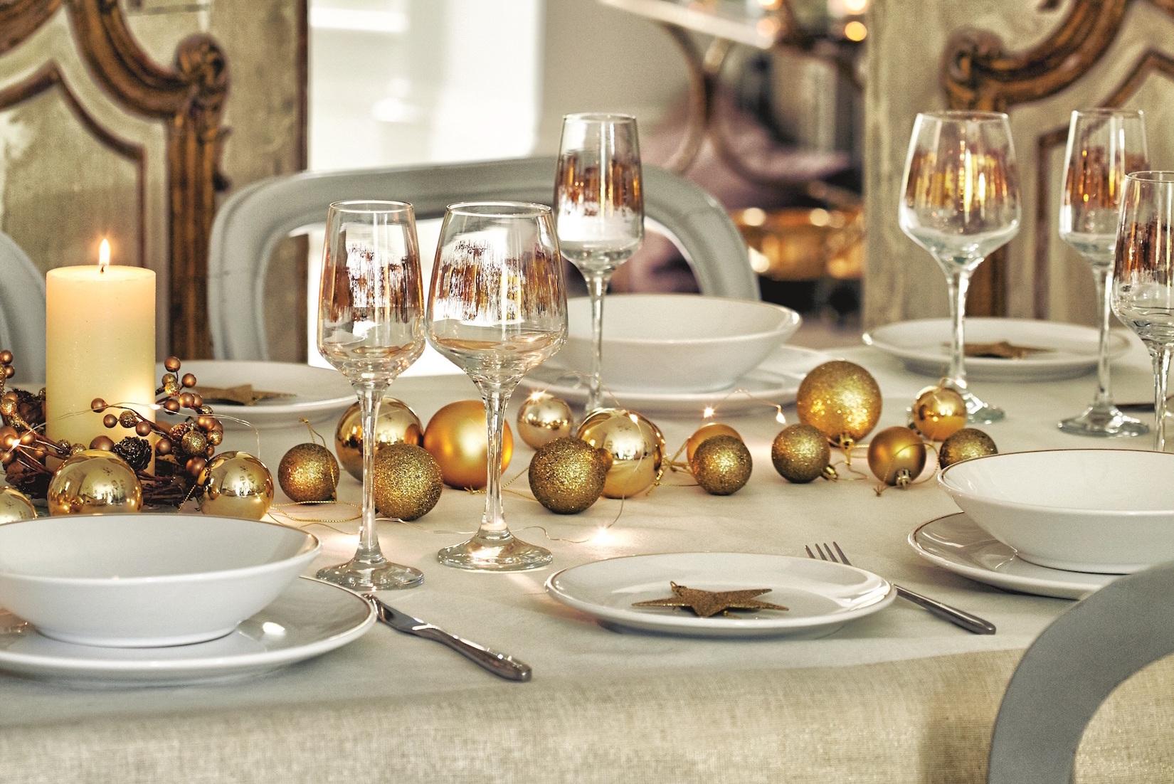 Štědrovečerní tabuli lze ozdobit různými způsoby. Sada metalických ozdob z vánoční kolekce F&F Home ladí se skleničkami na víno se zlatým zdobením.